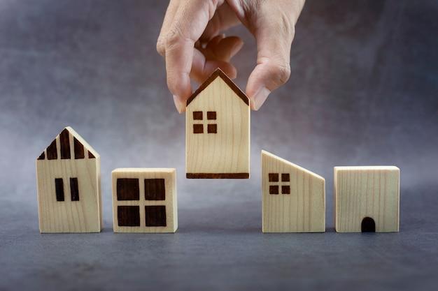 Main d'homme d'affaires choisissant le modèle de maison et prévoyant d'acheter une propriété