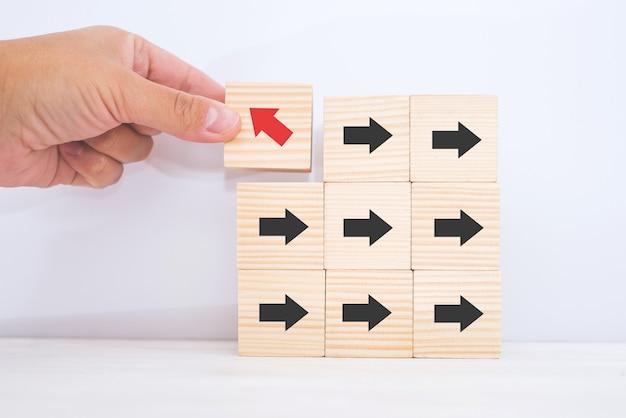 La main d'un homme d'affaires choisit un blog de jouets en bois cube avec des icônes de tête de flèche pointant vers des directions opposées pour le leader du changement d'entreprise vers les concepts de croissance et de réussite.