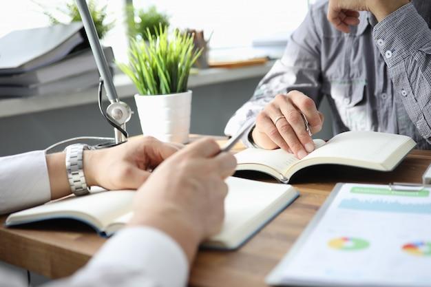 Main d'homme d'affaires en costume de remplissage et de signature avec un formulaire d'accord de partenariat avec un stylo argent coupé à un gros plan