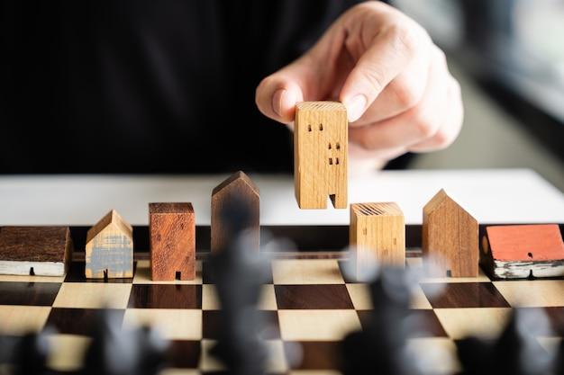 Main de l'homme d'affaires déménagement des modèles de bâtiment et de maison dans le jeu d'échecs