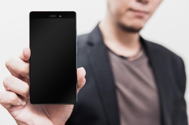 Main d'homme d'affaires sur écran vide de show smartphone avec un tracé de détourage à l'affichage
