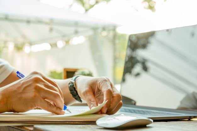 Main d'homme d'affaires écrit sur papier de cahier avec ordinateur portable sur la table.