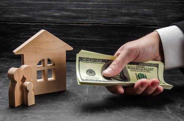 La main d'un homme d'affaires étend son argent à des figures de famille en bois et à une maison en bois.