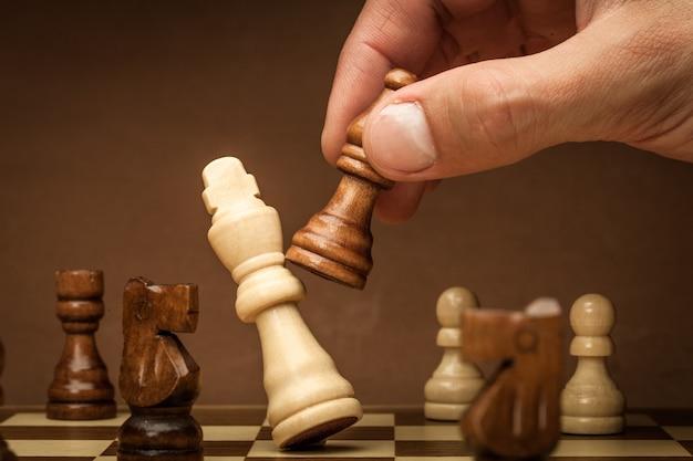 Main d'homme d'affaires jouant aux échecs se bouchent