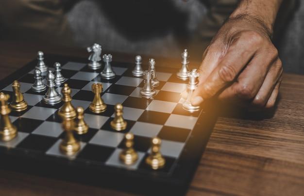 La main d'un homme d'affaires jouant aux échecs suppose la gestion de la stratégie