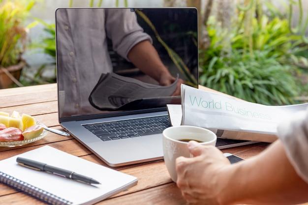 Main d'homme d'affaires sur le journal de lecture de café avec ordinateur portable sur la table.