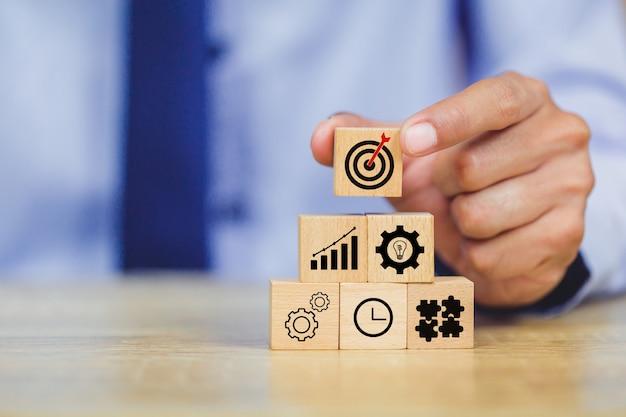 Main d'homme d'affaires mettant le bloc de bois sur le dessus avec le concept de réussite cible.