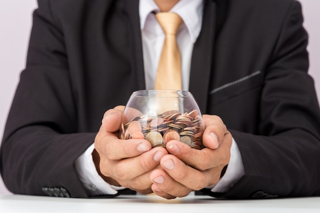 Main d'homme d'affaires mettant les pièces sur le verre, concept d'économiser de l'argent pour la comptabilité financière