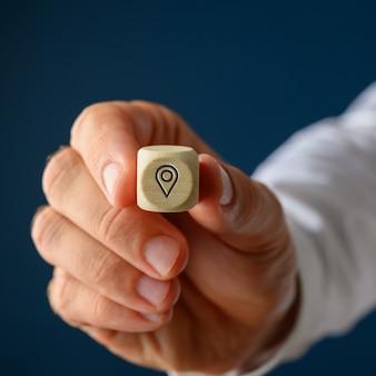 Main d'un homme d'affaires montrant un cube en bois avec symbole de broche de localisation dessus