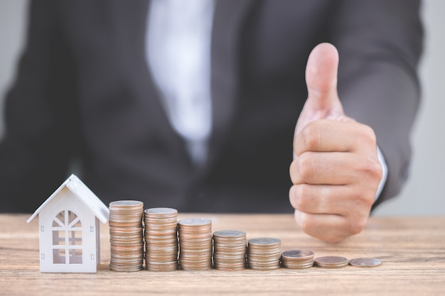 Main d'homme d'affaires montrer pouces avec de l'argent de pile de pièces intensifier de plus en plus