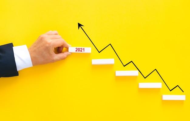 Main d'homme d'affaires organisant l'empilement de blocs de bois comme escalier avec flèche de croissance par an 2021.