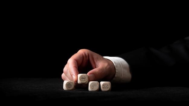 Main d'un homme d'affaires organisant quatre cubes en bois avec des icônes de contact et de communication sur eux d'affilée sur fond noir.