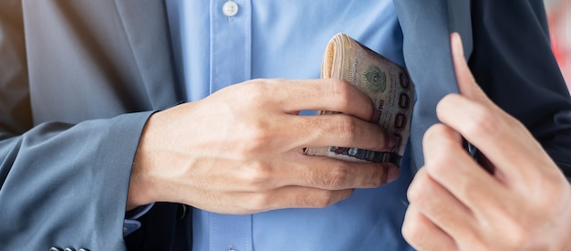 Main d'homme d'affaires sur la pile de billets de baht thaïlandais.
