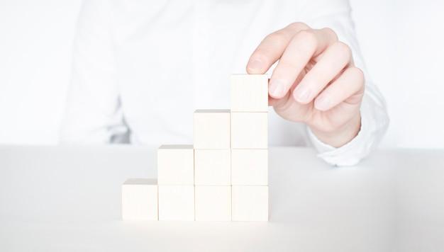 Main d'homme d'affaires plaçant ou tirant un bloc de bois rouge sur le bâtiment. planification d'entreprise, gestion des risques, solution, stratégie, concepts différents et uniques