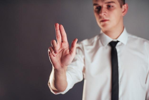 Main d'homme d'affaires pointant dans l'espace vide sur fond noir