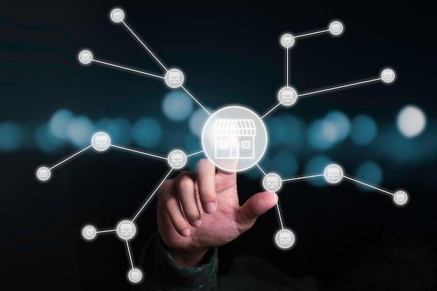 Main d'homme d'affaires pointant vers un magasin virtuel qui relie la ligne avec d'autres petits magasins, élargit et développe le concept de franchise.