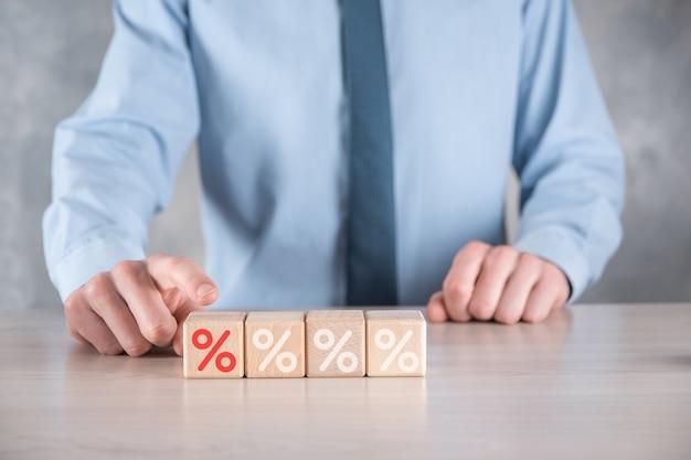 La main d'homme d'affaires prend un bloc de cube en bois montrant l'icône du symbole de pourcentage.