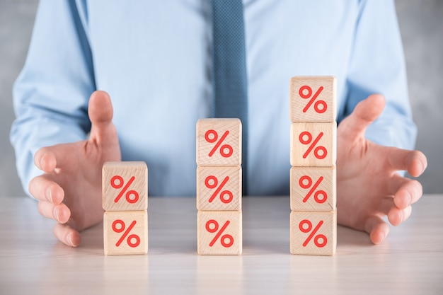 La main d'homme d'affaires prend un bloc de cube en bois montrant le symbole de pourcentage.