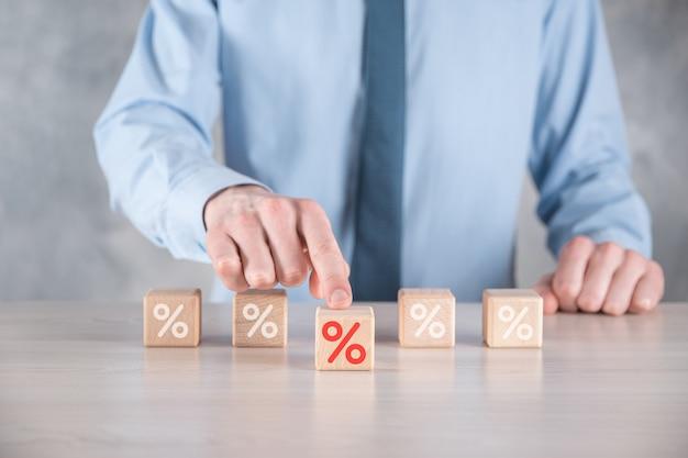 La main d'homme d'affaires prend un bloc de cube en bois représentant, montré l'icône de symbole de pourcentage. concept de taux d'intérêt financiers et de taux hypothécaires.