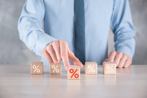 La main d'homme d'affaires prend un bloc de cube en bois représentant, montré l'icône de symbole de pourcentage.