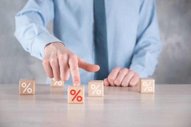 Main d'homme d'affaires prend un bloc de cube en bois représentant