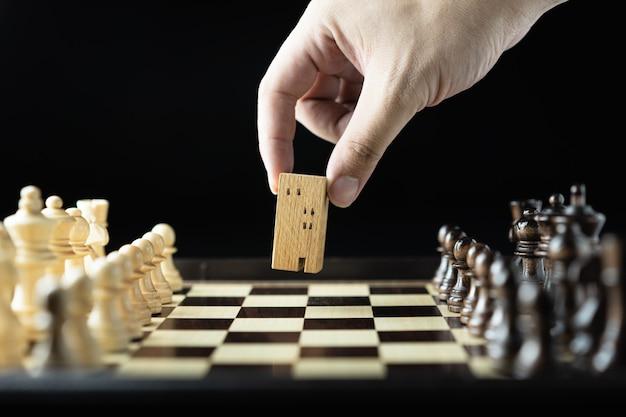 Main d'homme d'affaires se déplaçant d'échecs au bâtiment et aux modèles de maison dans le jeu d'échecs