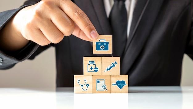 La main d'un homme d'affaires sélectionne une icône médicale sur un bloc de cube en bois