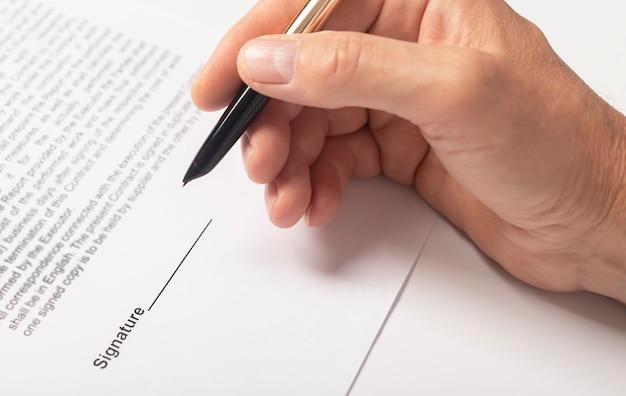 Main d'homme d'affaires avec un stylo sur le document agrandi.