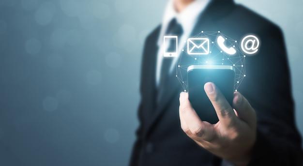 Main d'homme d'affaires sur téléphone intelligent avec l'icône de téléphone mobile, courrier, téléphone et adresse. centre d'appels du service clientèle contactez-nous concept