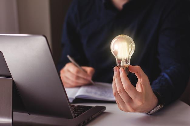 La main d'un homme d'affaires tenant une ampoule allumée et écrivant dans un cahier idée innovation