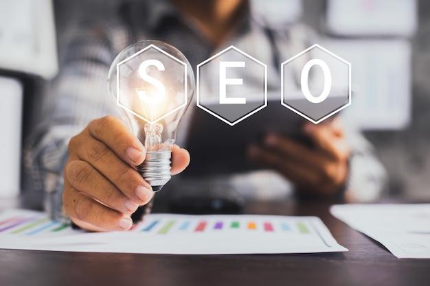 Main d'homme d'affaires tenant une ampoule avec un design de texte seo au premier plan