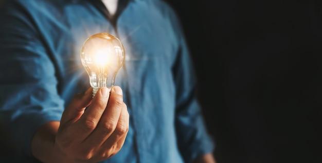 Main d'homme d'affaires tenant l'ampoule. idée alternative économie d'énergie