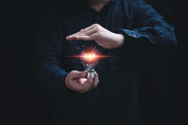 Une main d'homme d'affaires tenant une ampoule rougeoyante et une autre main la protégeant pour empêcher l'idée de pensée créative et le concept de brevet.