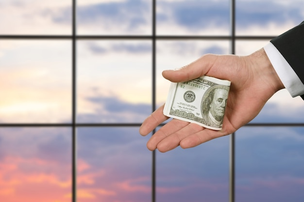 La main de l'homme d'affaires tenant de l'argent. dollars américains sur fond de coucher de soleil. des papiers qui changent la vie. prime de salaire du gestionnaire.