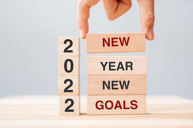 Main d'homme d'affaires tenant un bloc en bois avec du texte nouveaux objectifs du nouvel an 2022 sur fond de table. concepts de résolution, de stratégie, de solution, d'entreprise et de vacances