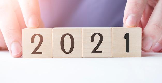 Main d'homme d'affaires tenant un bloc de cube en bois avec mot d'affaires 2021 sur table