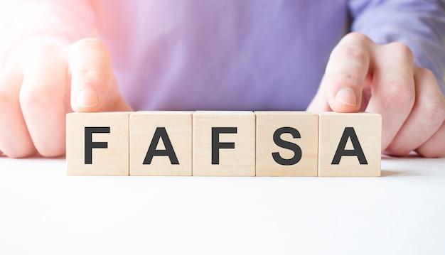 Main d'homme d'affaires tenant un bloc de cube en bois avec mot d'affaires fafsa sur fond de table.