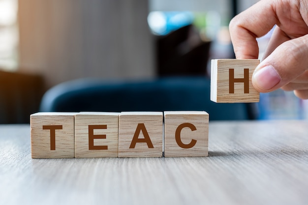 Main d'homme d'affaires tenant le bloc de cube en bois avec le mot entreprise d'enseignement. business, inspirer et motiver le concept