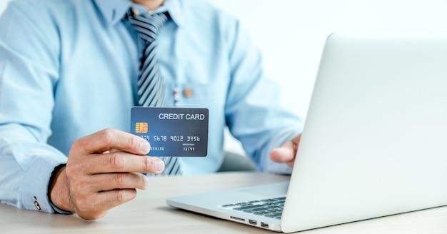 Main d'homme d'affaires tenant une carte de crédit pour faire des achats en ligne à domicile avec ordinateur portable, paiement en ligne, services bancaires sur internet, dépenser de l'argent pour les prochaines vacances.