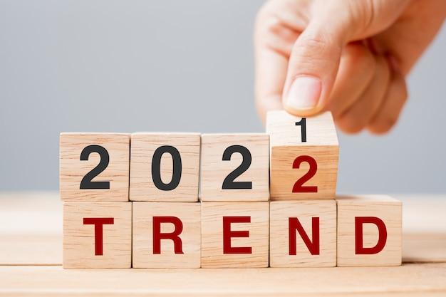 Main d'homme d'affaires tenant un cube en bois et renversant le bloc tendance 2021 à 2022 sur fond de table. résolution, planification, révision, changement, objectif et concepts de vacances du nouvel an