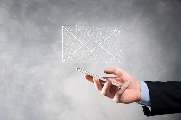 Main d'homme d'affaires tenant l'icône de courrier électronique, contactez-nous par courrier électronique de newsletter et protégez vos informations personnelles contre le courrier indésirable. centre d'appels de service client nous contacter concept.