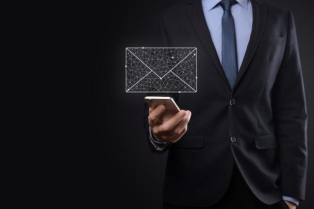 Main d'homme d'affaires tenant l'icône de courrier électronique, contactez-nous par courrier électronique de newsletter et protégez vos informations personnelles contre le courrier indésirable