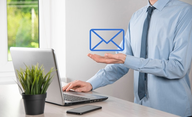 Main d'homme d'affaires tenant l'icône de courrier électronique, contactez-nous par courrier électronique et protégez vos informations personnelles contre les courriers indésirables. centre d'appels du service client contactez-nous concept.
