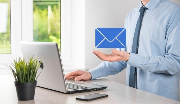 Main d'homme d'affaires tenant l'icône de courrier électronique, contactez-nous par courrier électronique et protégez vos informations personnelles contre les courriers indésirables. centre d'appels du service client contactez-nous concept