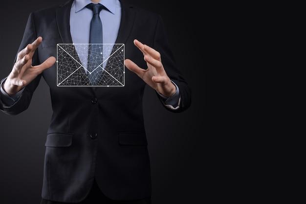 Main d'homme d'affaires tenant l'icône de courrier électronique, contactez-nous par courrier électronique et protégez votre