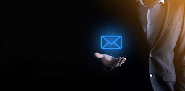 Main d'homme d'affaires tenant l'icône e-mail, contactez-nous par e-mail de newsletter et protégez vos informations personnelles