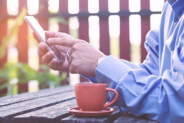 Main d'homme d'affaires tenant et jouant au smartphone près de tasse de café