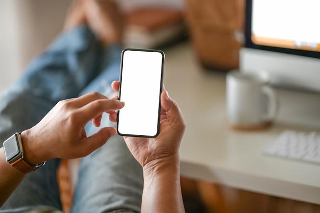 Main d'homme d'affaires tenant un téléphone mobile blanc blanc au bureau
