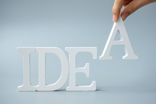 Main d'homme d'affaires tenant le texte d'idées en bois sur fond gris. nouveau concept de création, d'innovation, d'imagination, d'inspiration, de solution, de stratégie et d'objectif
