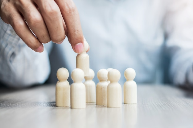 Main d'homme d'affaires tirant l'homme leader en bois de la foule d'employés. personnel, entreprise, gestion des ressources humaines, recrutement, travail d'équipe, stratégie et leadership concepts